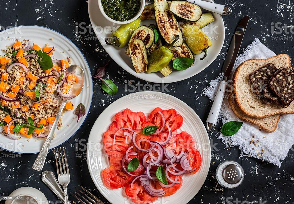 Vegetarian table -  quinoa, pumpkin salad, tomatoes, grilled eggplants, peppers stock photo
