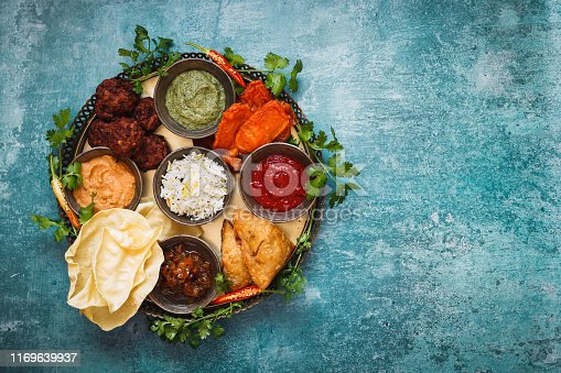 Vegetarian Thali. Indian appetizers and snacks: pakora, samosas and bhaji served with chutneys and other dipping sauces  on rustic surface. Top view, blank space