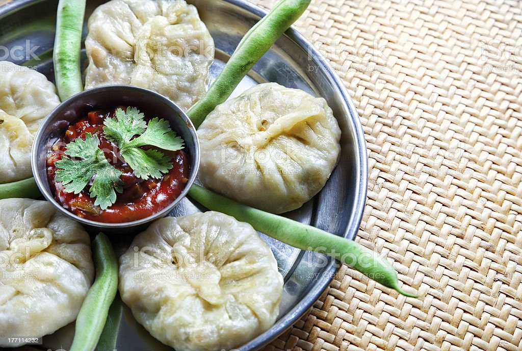 Vegetarian Tibetan momo with beans Tibetan traditional dumpling momo served with red chatni and green raw beans on the small wooden table. Free space for your text Appetizer Stock Photo