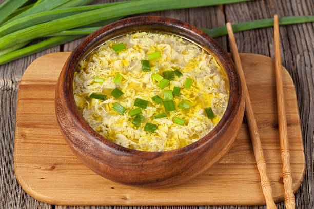 Vegetarian traditional asian drop egg soup with broth in wooden stock photo