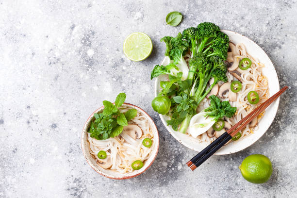 vegetarian traditional vietnamese soup pho bo with herbs, rice noodles, broccolini, bok choy, bean sprouts, mushrooms. vietnam national dish. asian food concept. - pho soup stock photos and pictures