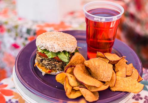 Vegetarian vegan burger, sweet potato fries chips, and raspberry lemonade at a street food market