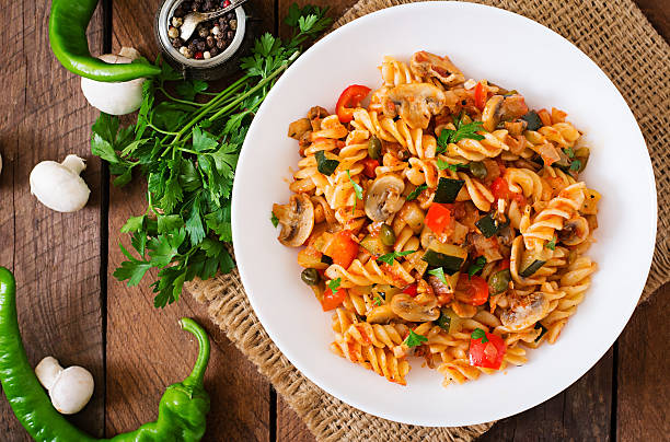 Vegetarian Vegetable pasta Fusilli with zucchini, mushrooms and capers Vegetarian Vegetable pasta Fusilli with zucchini, mushrooms and capers in white bowl on wooden table. Top view fusilli stock pictures, royalty-free photos & images