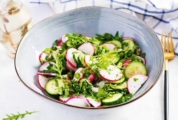 Vegetarian vegetable salad of radish, cucumbers, arugula and green onions. Healthy  vegan food. stock photo