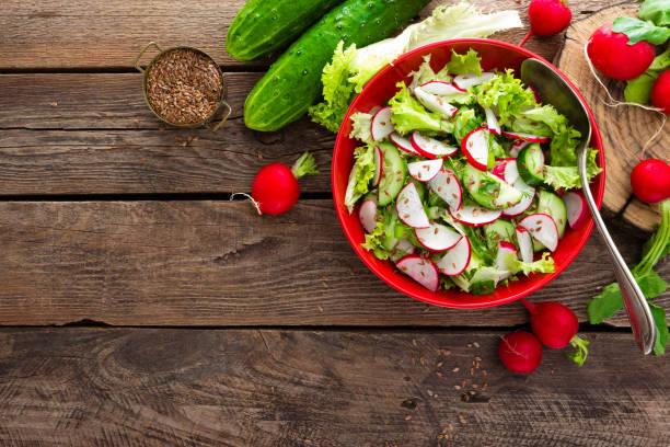 vegetarische gemüse salat aus rettich, gurken, kopfsalat und leinsamen. gesunde vegane ernährung. ansicht von oben - radieschen salat stock-fotos und bilder