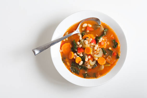 Vegetarian Vegetable Soup Vegan vegetable soup with kale, white beans, tomatoes, celery, carrots, red peppers. vegetable soup stock pictures, royalty-free photos & images