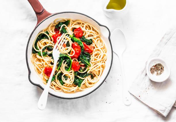 vegetarische vollkorn spaghetti nudeln mit cherry-tomaten und spinatsauce in einer gusseisernen pfanne auf einem weißen hintergrund, ansicht von oben. textfreiraum, gesunde ernährung food konzept - spaghetti mit spinat stock-fotos und bilder