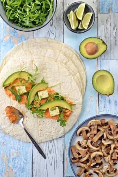 vegetarische packung mit hummus, tofu, avocado und pilzen - veggie wraps stock-fotos und bilder