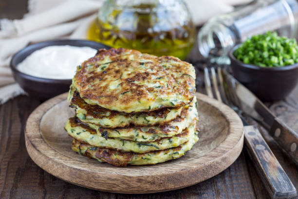 Vegetarian zucchini fritters or pancakes, served with greek yogurt and green onion on wooden background, horizontal stock photo