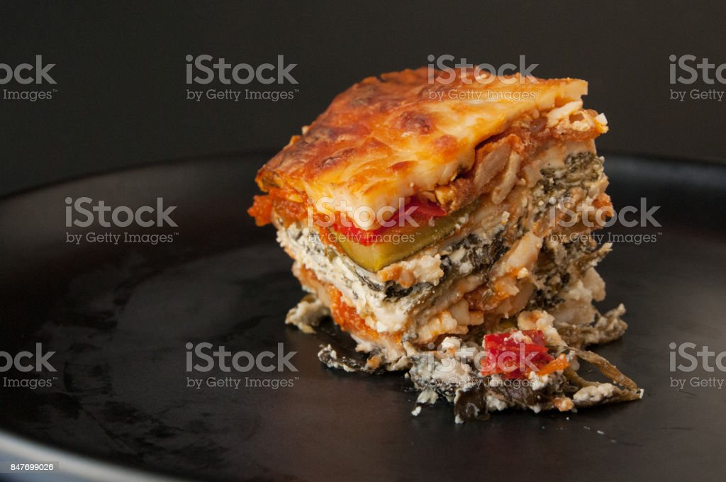 Vegetarien and gluten-free lasagna portion on black plate stock photo