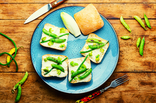 Vegetable bruschetta with broccoli,green peas and asparagus beans on rural wooden table.Vegetarian food