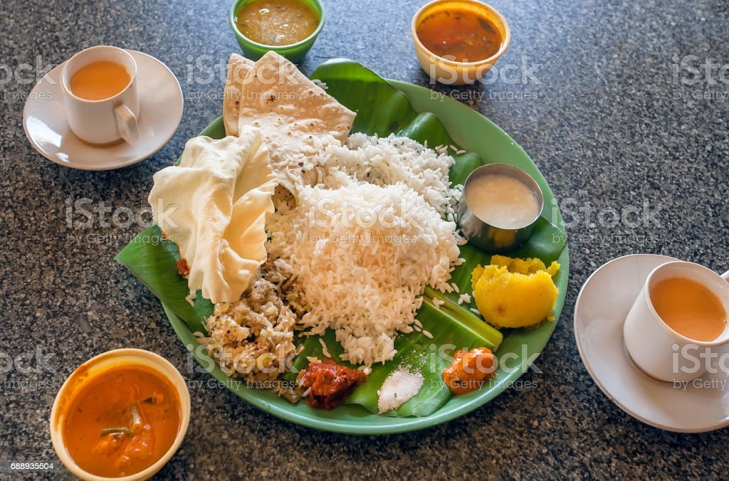 Vegeterian Indian food thali with chutney or pickle, rice, spicy vegetables and sweets on palm leaf in indian cafe. stock photo
