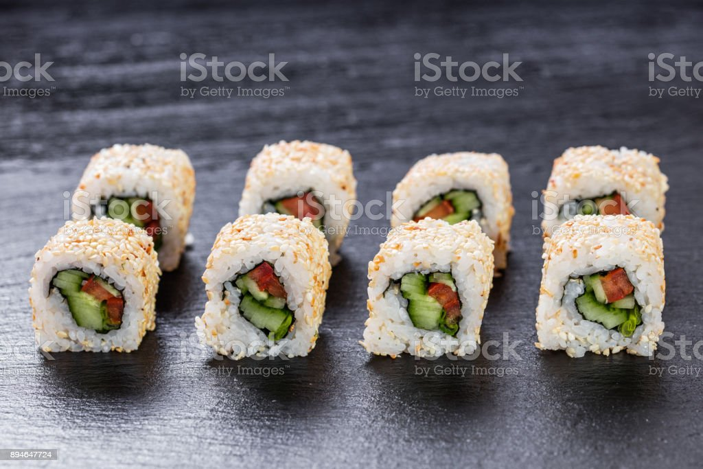 Vegeterian makizushi roll with cucumber and tomato arranged on slate plate background stock photo
