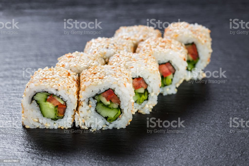 Vegeterian makizushi roll with cucumber and tomato over slate plate background stock photo