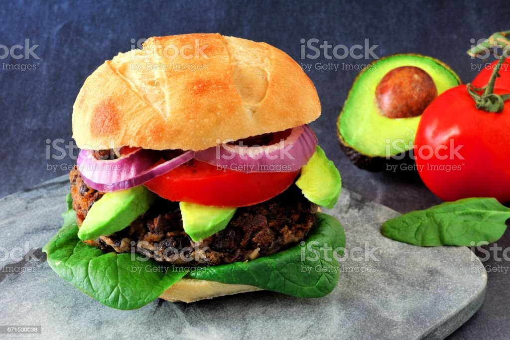 Veggie burger with avocado and spinach on a dark background stock photo