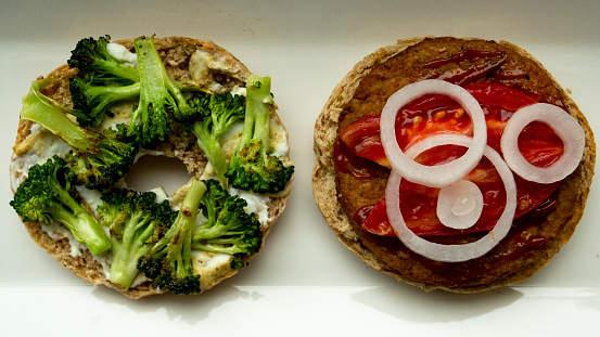 Veggie burger dressed with broccoli, sliced tomato and onion on toasted bagel