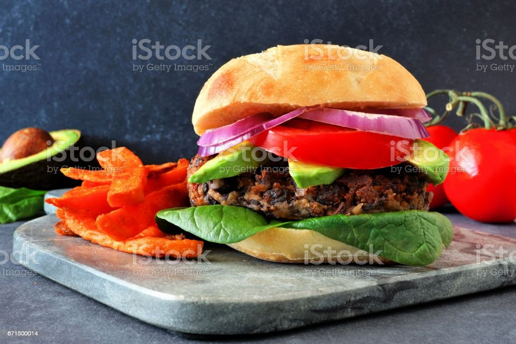 Veggie burger with sweet potato fries on a dark background stock photo