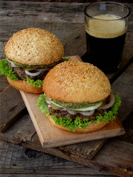 veggie burgers with a chop of black beans, lettuce, pickled onions, cucumber on a brown wooden background. stock photo