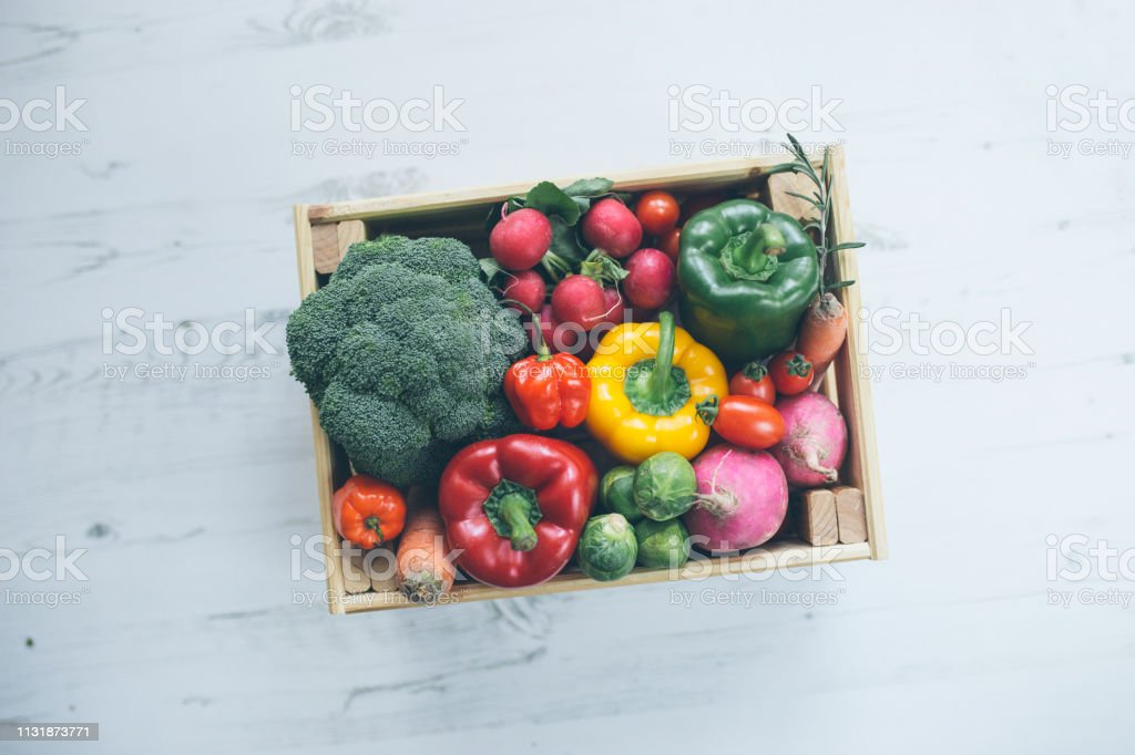 veggies in wood box with white wood backdrop