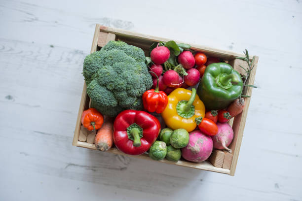 Veggies in wood box with white wood backdrop stock photo