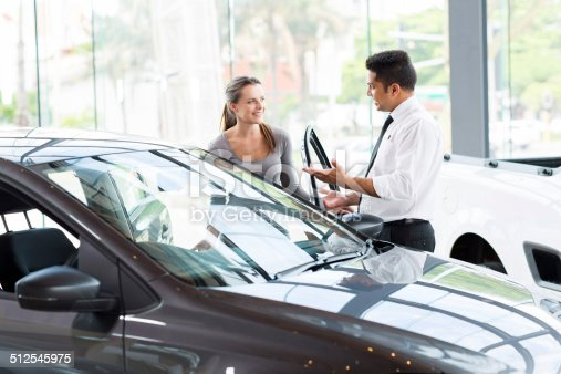 istock vehicle dealer showing young woman new car 512545975