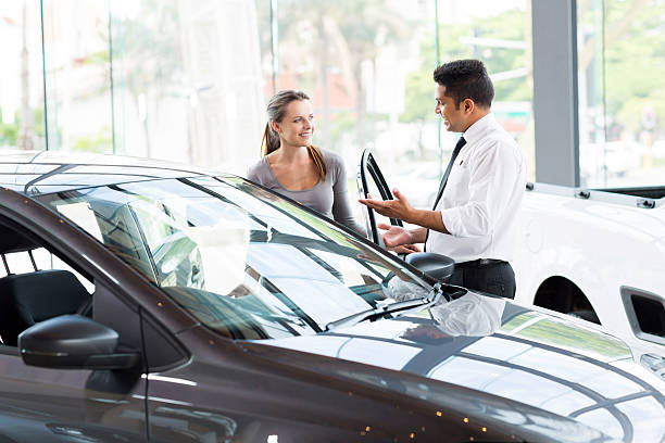 vehicle dealer showing young woman new car friendly vehicle dealer showing young woman new car car salesperson stock pictures, royalty-free photos & images