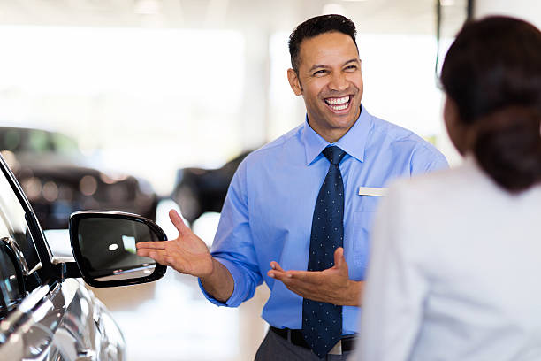 vehicle dealer showing young woman new car stock photo