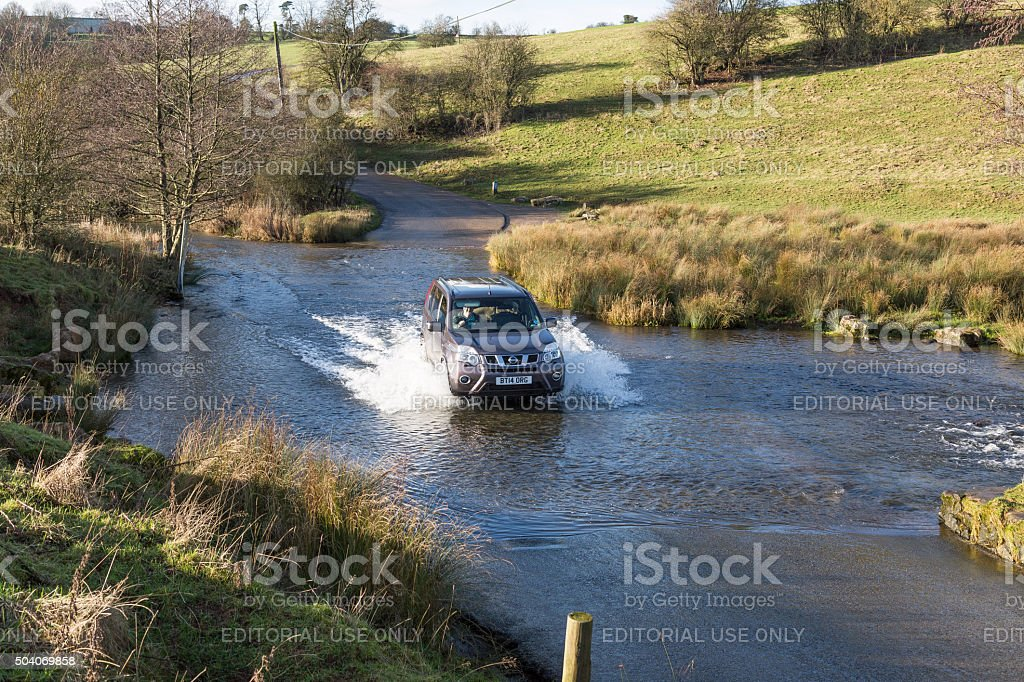 4WD vehicle driving through a road ford stock photo
