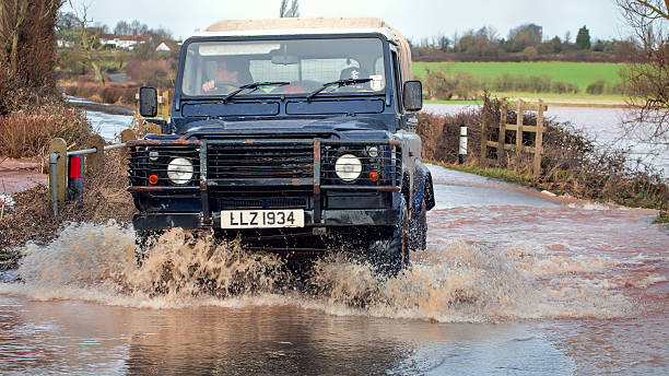 Vehicle Driving Through Flood Water On Road stock photo
