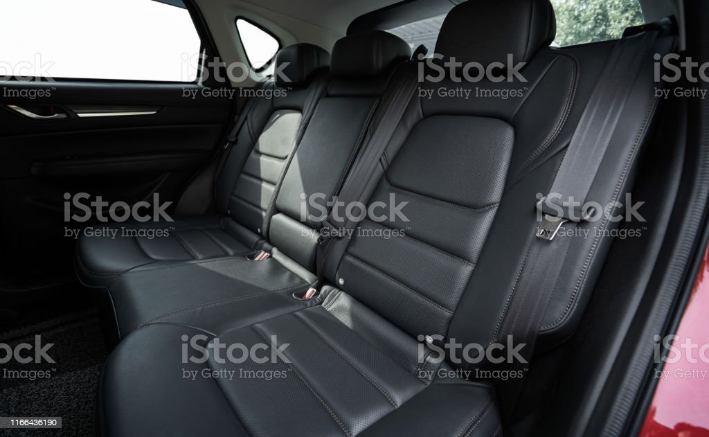 Closeup of a modern car interior with the black leather rear seats