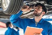 istock Vehicle service maintenance handsome man checking under car condition in garage. Automotive mechanic pointing flash light on wheel following maintenance checklist document. Car repair service concept 1207296834