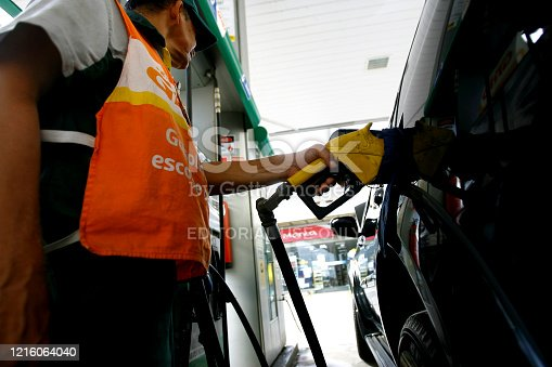salvador, bahia / brazil - october 8, 2014: gas station attendant is seen filling up a vehicle at petrol stations in the Petrobras network, in the city of Salvador.