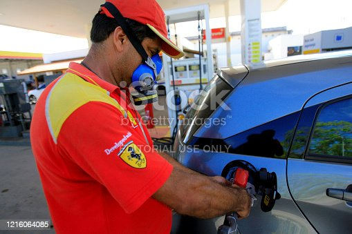 ilheus, bahia / brazil - february 14, 2014: gas station attendant wears a mask during vehicle refueling at Shell gas stations, in the city of Ilheus.