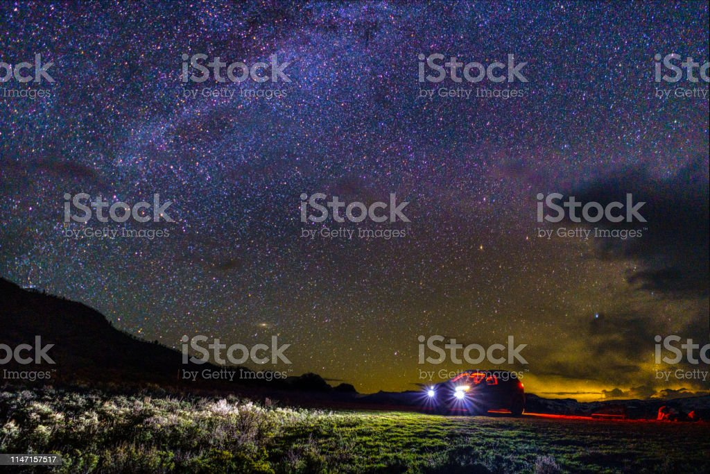 SUV Vehicle with Lights on Under Stars and Dark Sky - Stargazing on a...