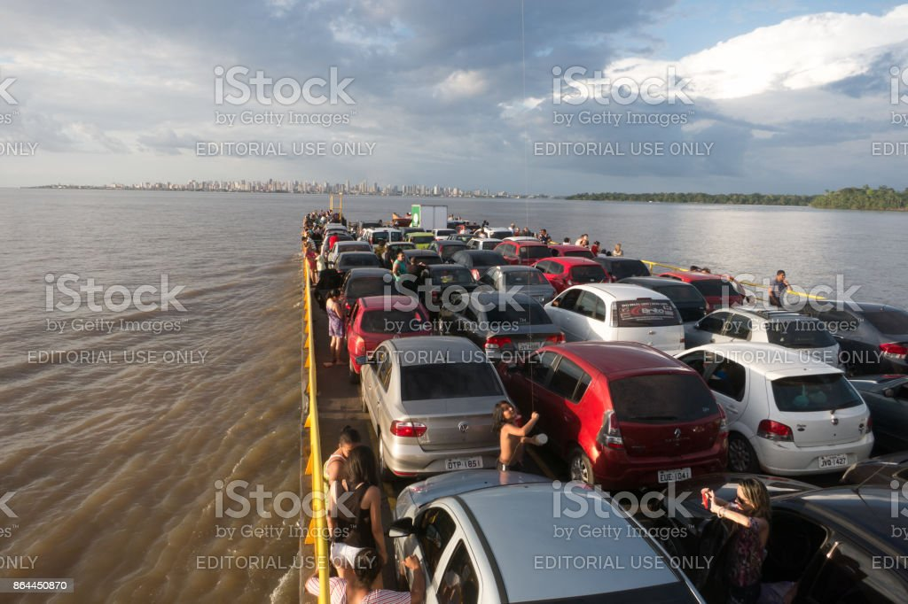Vehicles and people transportation on a ferry crossing an amazonian river stock photo
