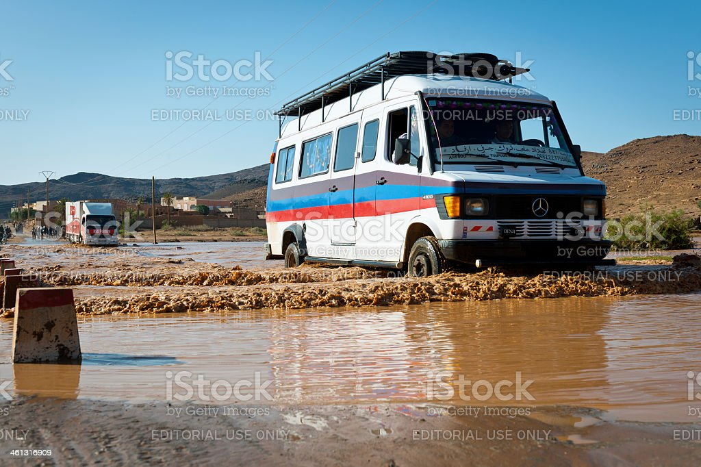 Vehicles Crossing Flooded Road in Moroccan Desert , Africa royalty-free stock photo