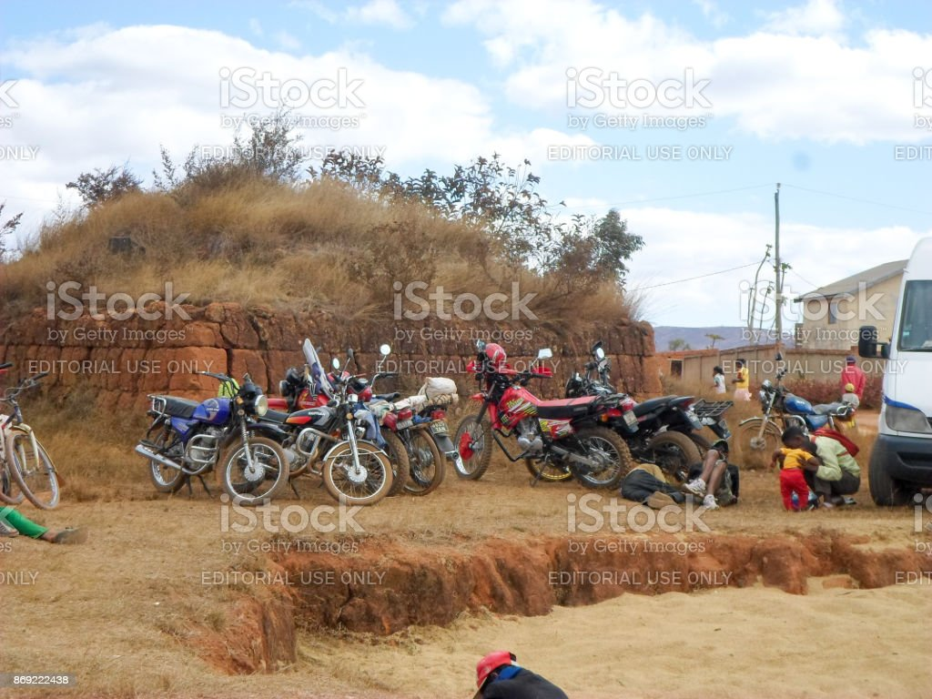 Vehicles made up of motorcycles, bicycles and automobiles waiting in front of a grave for the end of the rite of 'famadihana' (exhumation) stock photo