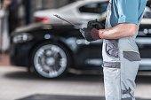 Caucasian Auto Service Worker with Documentation. Vehicles Maintenance Work