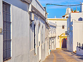 La Corredera, a typical street of whitewashed walls of Vejer de la Frontera downtown, with Merced de Santa Catalina church in the background. Cadiz province, Andalusia, Spain.