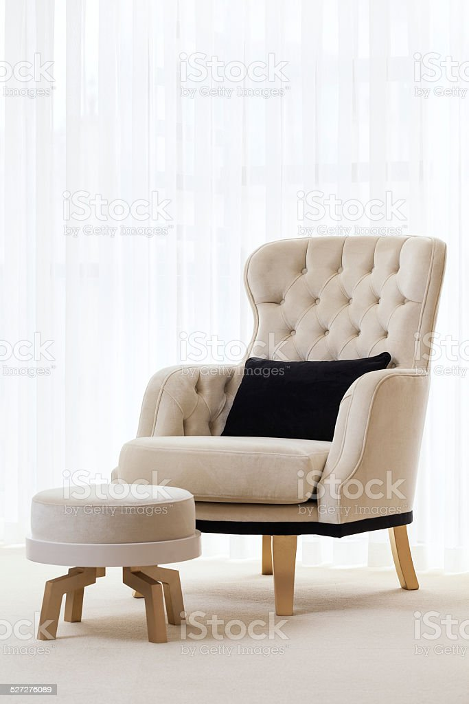Velvet armchair and foot rest stays in front of window stock photo