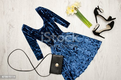 Velvet blue dress, black shoes, clutch and a bouquet of daffodils. Fashionable concept. Wooden background. Top view