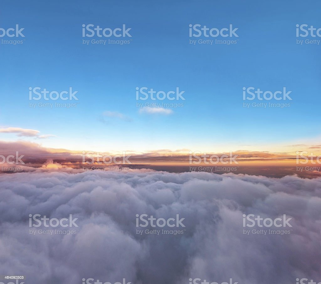 Velvet sunset above cloudscape from airplane stock photo