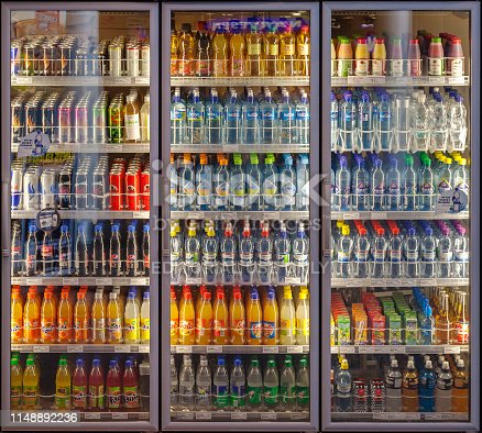 Oslo, Norway-February 22, 2011:  Illuminated three doors vending machine / chiller cabinet, cooling shelves with a diverse range of soft drinks in a shop on the main train stationIn Oslo, Norway. Packaging to be returned for recycling for new bottles and other products
