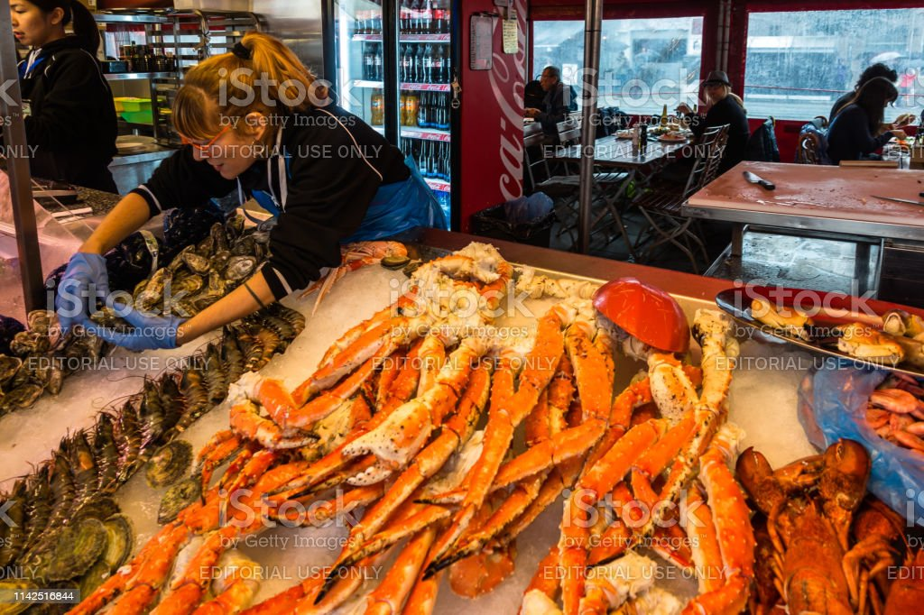 A vendor at Bergen fish market selling crabs, lobsters and other...
