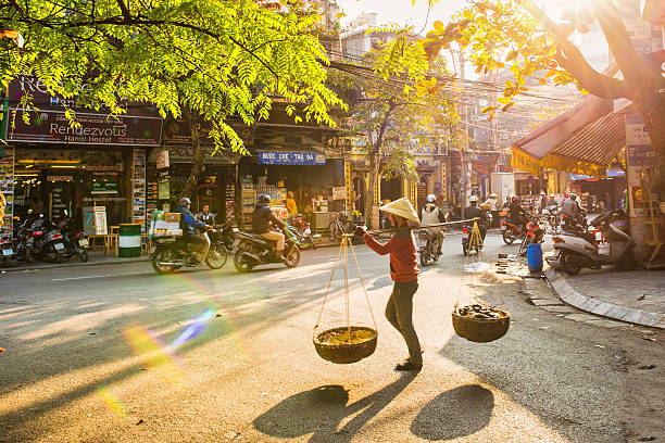 Vendor in Hanoi Hanoi, Vietnam - 13 January, 2015: A vendor is walking into old street hanoi stock pictures, royalty-free photos & images