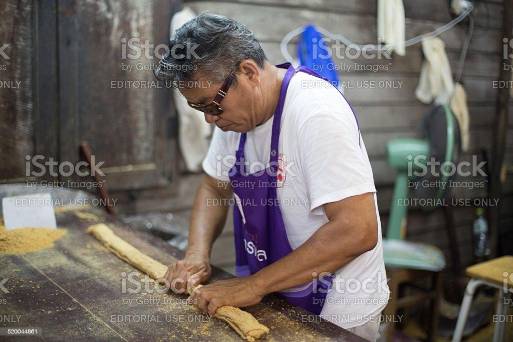 Vendor prepares peanut candy, Talad Noi, Bangkok, Thailand. stock photo
