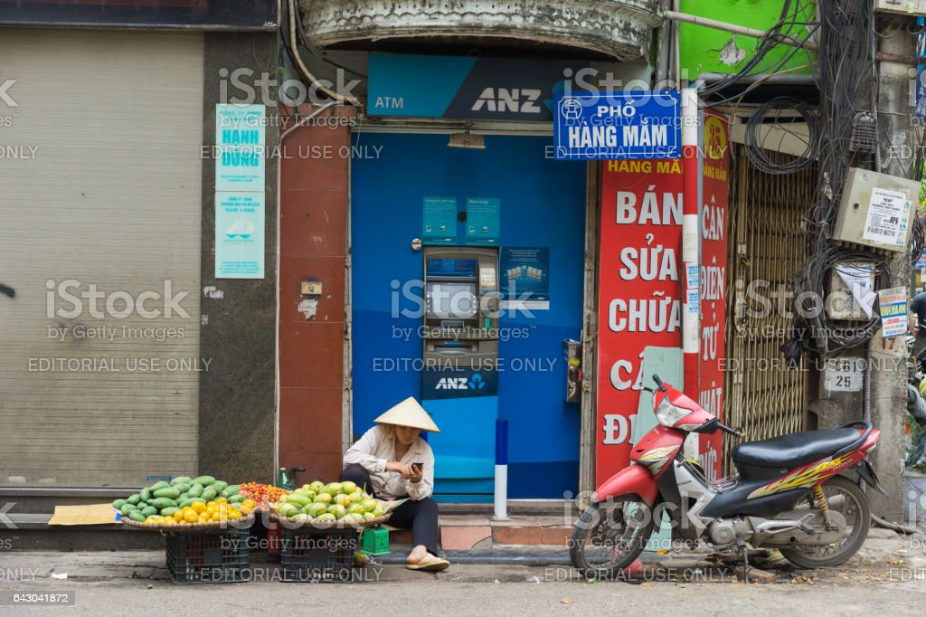 Hanoi, Vietnam - Apr 5, 2015: Vendor sales fruit in front of ANZ ATM in Hang Mam street, Hanoi stock photo