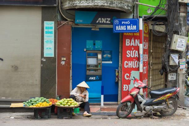 Hanoi, Vietnam - Apr 5, 2015: Vendor sales fruit in front of ANZ ATM in Hang Mam street, Hanoi stock photo