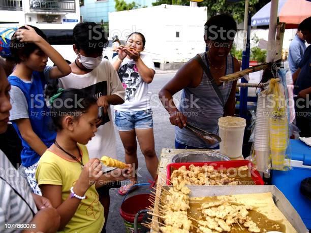 Vendor sells assorted street food in his food cart during the town picture id1077860078?b=1&k=6&m=1077860078&s=612x612&h=towr4ltij4mochl4qjfz uj0jwnxetlb0g37alrbbmm=