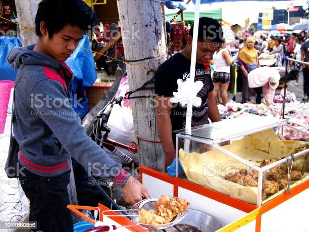 Vendor sells assorted street food in his food cart during the town picture id1077860856?b=1&k=6&m=1077860856&s=612x612&h= ojyl7ox9o2zgcuhzsi7cglruo03 dt cpoglvk ggc=
